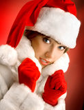 Attractive Girl in a White Fur Coat and Santa Claus Hat on the R Stock Photography