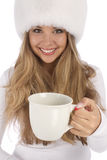 Attractive girl in white fur hat gives white mug Royalty Free Stock Photography