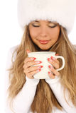 Attractive girl in white fur hat with white mug Royalty Free Stock Images