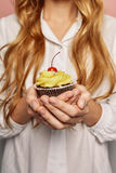 Attractive girl in a white shirt is holding cupcakes Stock Images