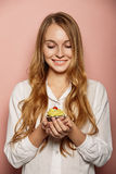 Attractive girl in a white shirt is holding cupcakes Stock Photo