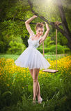 Attractive girl in white short dress posing near a tree swing with a flowery meadow in background. Blonde young woman. With ballerina dress under a tree in a Royalty Free Stock Photography