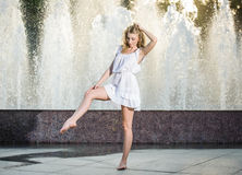 Attractive girl in white short dress sitting in front of a fountain in the summer hottest day Royalty Free Stock Photo