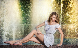 Attractive girl in white short dress sitting on parapet near the fountain in the summer hottest day Royalty Free Stock Photo