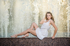 Attractive girl in white short dress sitting on parapet near the fountain in the summer hottest day Stock Photos
