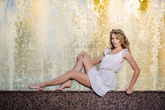 Attractive girl in white short dress sitting on parapet near the fountain in the summer hottest day Stock Image