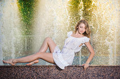 Attractive girl in white short dress sitting on parapet near the fountain in the summer hottest day Royalty Free Stock Images