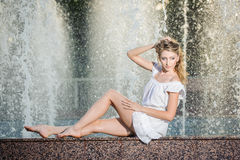 Attractive girl in white short dress sitting on parapet near the fountain in the summer hottest day Stock Photography
