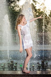 Attractive girl in white short dress sitting on parapet near the fountain in the summer hottest day Royalty Free Stock Image