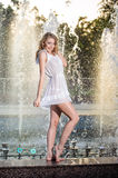 Attractive girl in white short dress sitting on parapet near the fountain in the summer hottest day Royalty Free Stock Photography