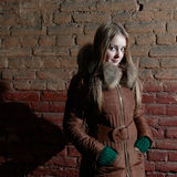 Attractive girl in winter near brick wall Royalty Free Stock Photo