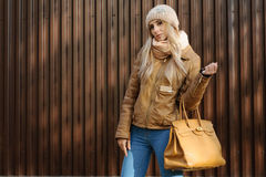 Attractive girl in wool hat leather jacket with beige bag. Attractive girl in wool hat and leather jacket, jeans with beige bag stands near the brown fence on stock photos