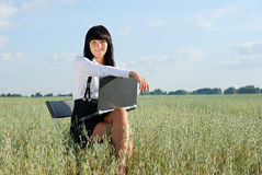 Attractive girl working on computer in nature. Young attractive girl with laptop on  rural field Stock Image