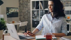 Attractive girl working with laptop computer and writing in notebook in office. Sitting at desk looking at screen. Youth, business and workplace concept stock video