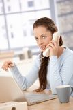 Attractive girl working on laptop talking on phone Royalty Free Stock Photos