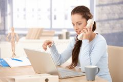 Attractive girl working on laptop talking on phone Royalty Free Stock Photo