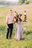Attractive girl in wreath sitting on swing with flowers, man standing next her royalty free stock image