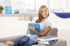 Attractive girl writing notes at home smiling royalty free stock image