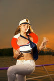 Attractive girl on a yacht. With a life buoy on her neck Royalty Free Stock Photo