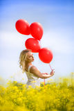 Attractive girl in yellow flowers with balloons. Attractive girl standing in yellow flowers with balloons Royalty Free Stock Photo