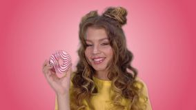 Attractive girl in a yellow shirt posing with a donut winks and smiling while looking at the camera. Attractive girl in a yellow vest with long hair poses with a stock video footage