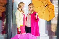 Attractive girlfreinds carrying the umbrellas Stock Image