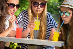 Attractive girlfriends enjoying cocktails in an outdoor cafe, friendship concept stock photography