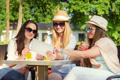 Attractive girlfriends enjoying cocktails and using wireless connection on digital tablet. Three attractive girlfriends enjoying cocktails and using wireless Stock Image