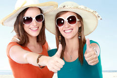 Attractive girlfriends in the summer day showing thumb up Stock Photography