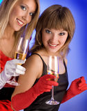 Attractive Girls With Champagne on the Blue Background. Royalty Free Stock Image