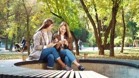 Happy girls browsing social media using smartphones in public park