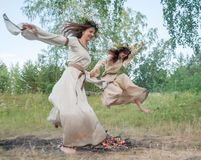 Attractive girls jump through fire Stock Photos