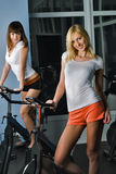 Attractive girls relax on bicycle simulators Stock Photos