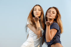 Attractive girls sending blow kisses. Young attractive girls sending blow kisses outdoor Royalty Free Stock Images