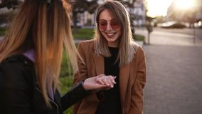 An attractive girls sitting on the street. Best friend shows off the engagement ring given to her by lover. Girl in. Stylish sunglasses shows her hand witha stock footage