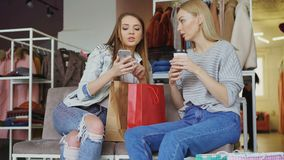 Attractive girls are sitting together in women`s clothing shop. They are drinking coffee, chatting carelessly and using. Smartphone. Nice boutique, colourful stock video
