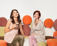 Attractive girls on sofa with coffee mugs laughing Royalty Free Stock Photos