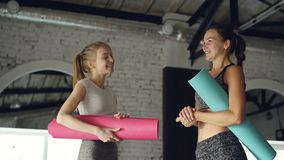 Attractive girls are talking and laughing in large modern sports center. Women are holding colorful yoga mats and. Wearing fashionable sports clothing. Fun in stock video footage