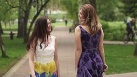 Attractive girls walking through the Park and smile. girlfriends spend time together outdoor. girls in bright summer. Attractive girl walking through the Park stock video footage