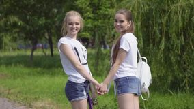 Attractive girls walking through the Park and smile. girlfriends spend time together outdoor. Slow motion stock video