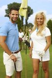 Attractive golfers on the green. Attractive, young golfers standing on the green, smiling, looking at camera stock photography
