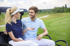 Attractive golfing couple talking Royalty Free Stock Photography