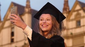 Attractive graduate girl taking selfie on graduation day holding diploma. Close up. Slow motion.Attractive graduate girl taking selfie on graduation day holding stock video