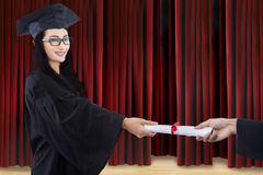 Attractive graduate given certificate on stage Stock Photography