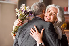 Attractive grandma smiling at the camera while hugging her husband Stock Photo