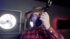 Attractive grey eyed man with beard with mexican hat holds microphone and sings. Attractive young male vlogger with beard put on stylish mexican hat and red stock footage