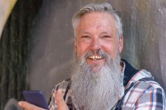 Attractive bearded man with a vivacious smile. Attractive grey-haired bearded man in a plaid shirt with a lovely vivacious smile holding a mobile phone Stock Photography