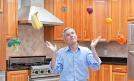 Attractive grey haired man thinking about diet. An attractive man with grey hair thinking about his diet, nutrition, and healthy foods such as fruit and stock image