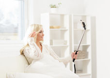 Attractive grimacing girl taking selfie holding a selfie stick Royalty Free Stock Images