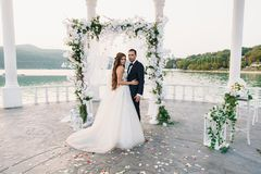 Attractive groom and bride at wedding day ceremory with arch and lake on background stands together. Beautiful newlyweds. Young women in white dress and long Royalty Free Stock Image
